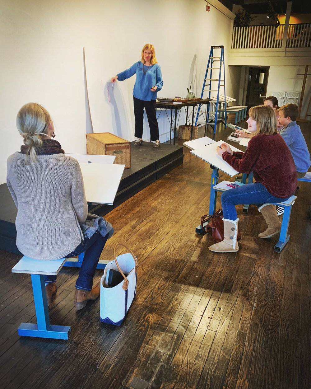 Pictured: Our co-founder, Michelle Radford, teaches an evening Beginning Drawing class to a group of students.