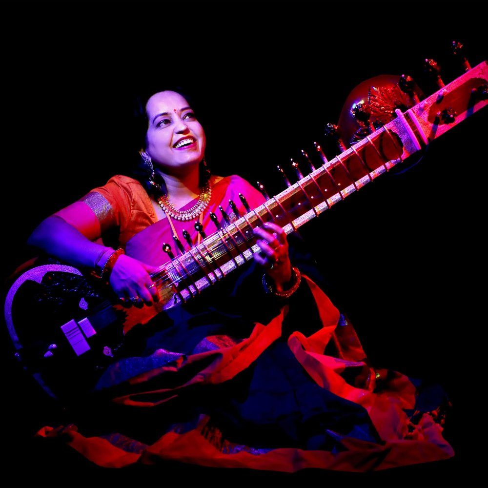 "Sarita - Sarita McHarg has a PhD in music, a masters (sitar) and has played the sitar for 20 years. She was born in Ujjain in India and has performed with Indian and Western musicians in Australia and overseas. Sarita comes from a family of professional musicians and vocalists. ""Kirtan brings everyone together no matter where we come from. When we chant together we let go of our egos.""Instrument: Sitarsaritamcharg.com"