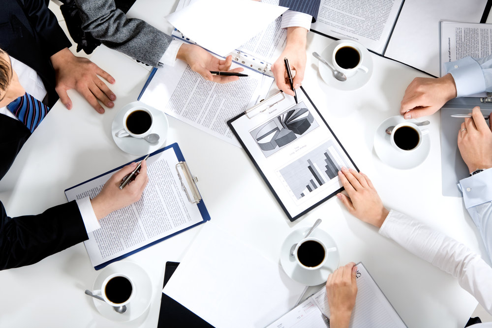 Group of people in meeting reviewing graphs and drinking coffee
