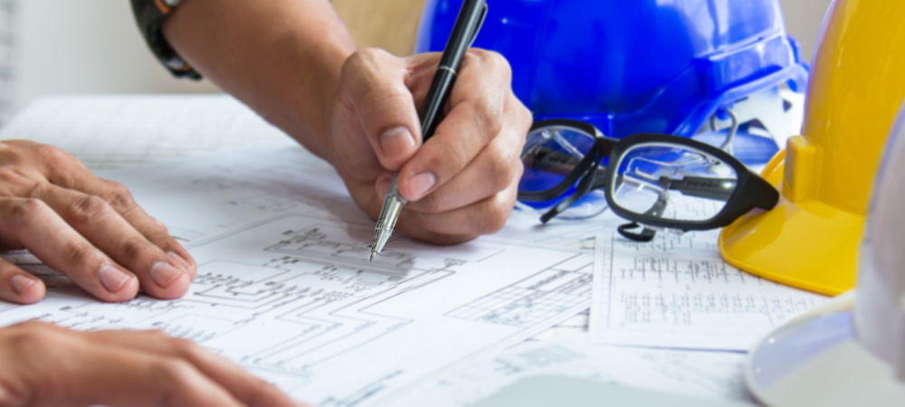 Close up of construction plans; man's hands taking notes; hard hats on a table in the background.