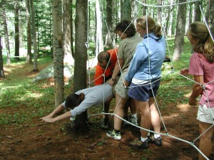 adult participants support each otehr through spider web initiative outdoor low team building challenge