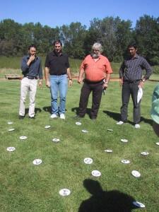 diverse group of men work to solve outdoor team building challenge