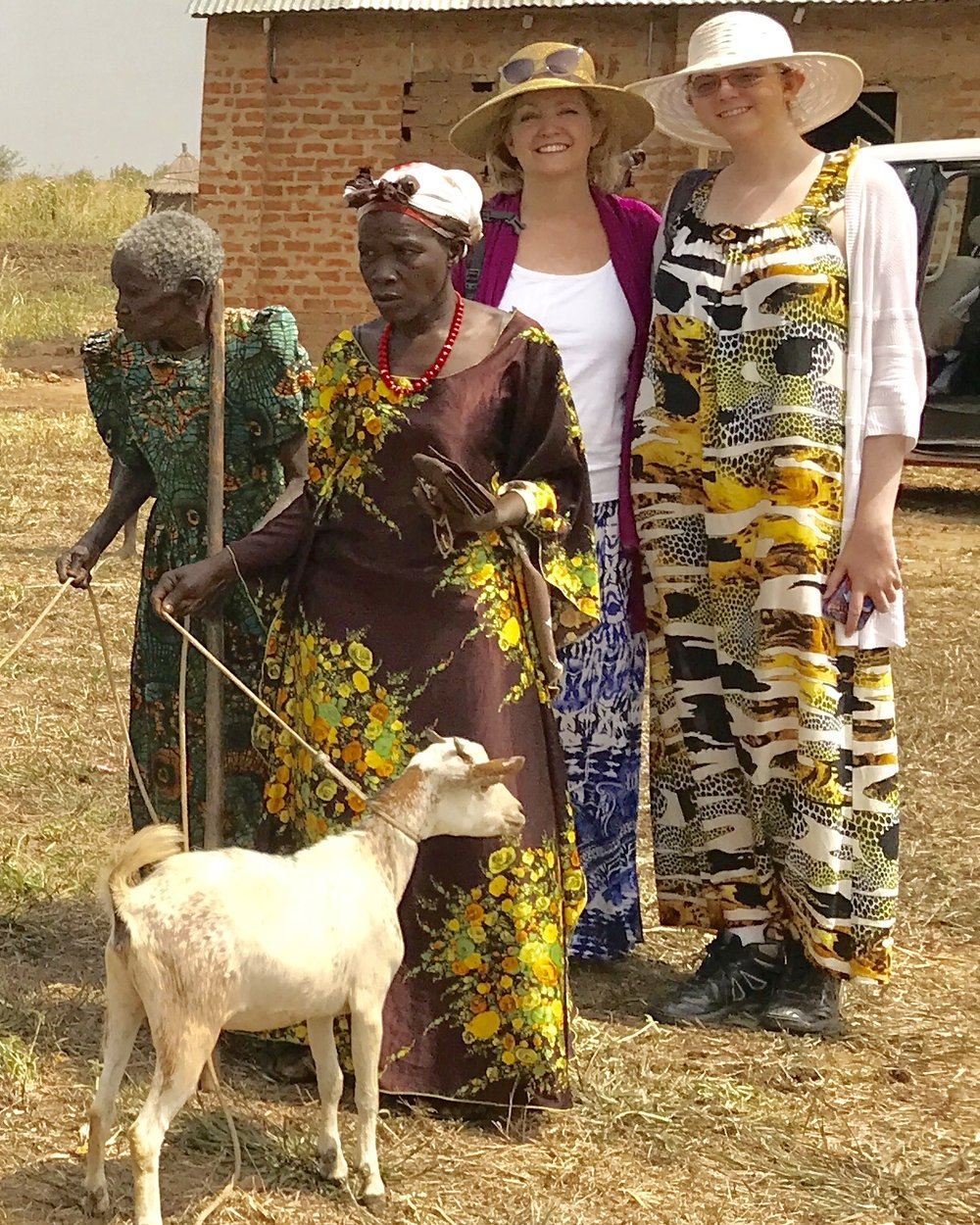 Tobi (middle right) and her daughter (right) posing with new beneficiaries and their goats.