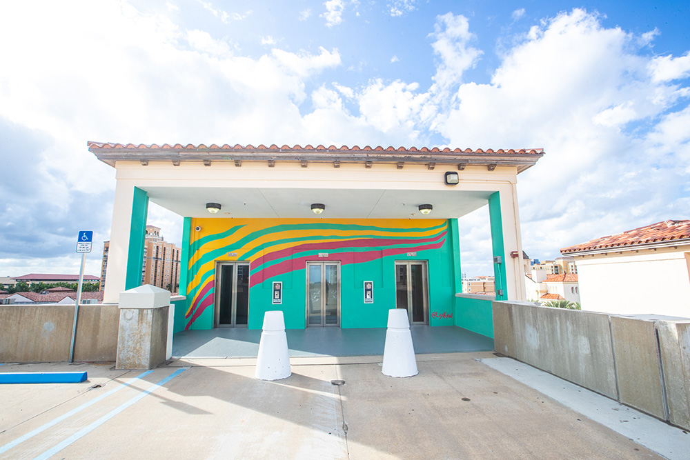 west palm waves - LISA KAWWest Palm Waves represents the energy of our thriving city. In constant undulation, we are perpetually moving and expanding. Our connection to the water recharges us and propels us forward. Water is life, and the city is full of it. Located on the fourth floor of the garage, the mural reminds us of the power and beauty of our vibrant community.Location: Hibiscus Garage, top level
