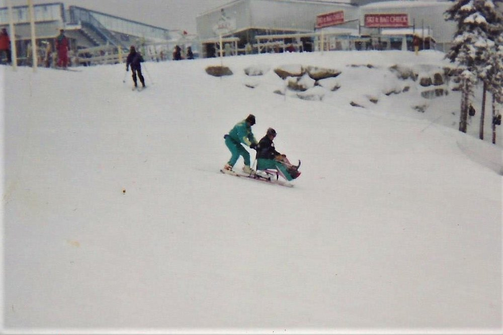 Sit-skiing with a volunteer.