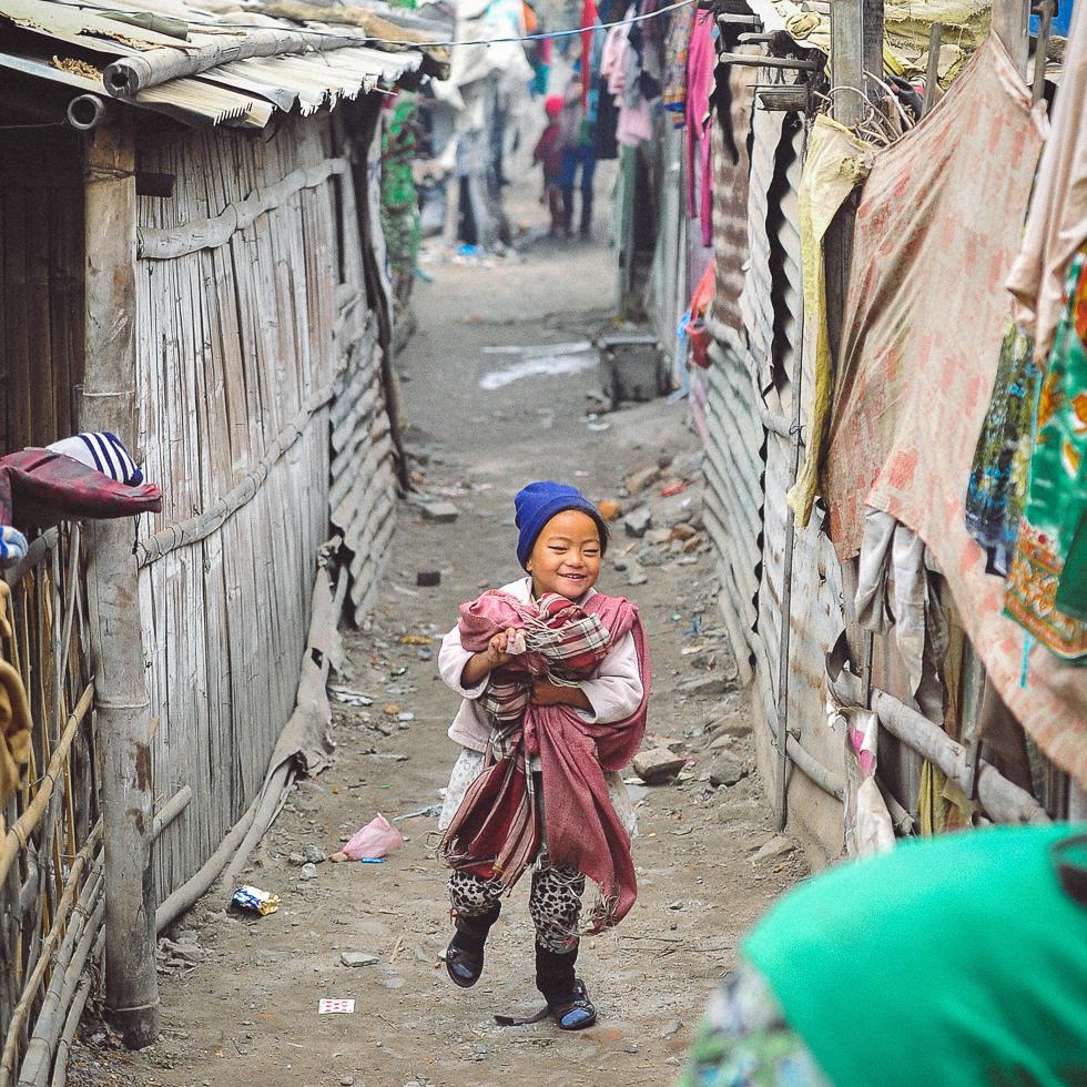 A sweet young girl runs through the homes of Balkhu Slum Settlement in Kathmandu | photo © touchnepal.org