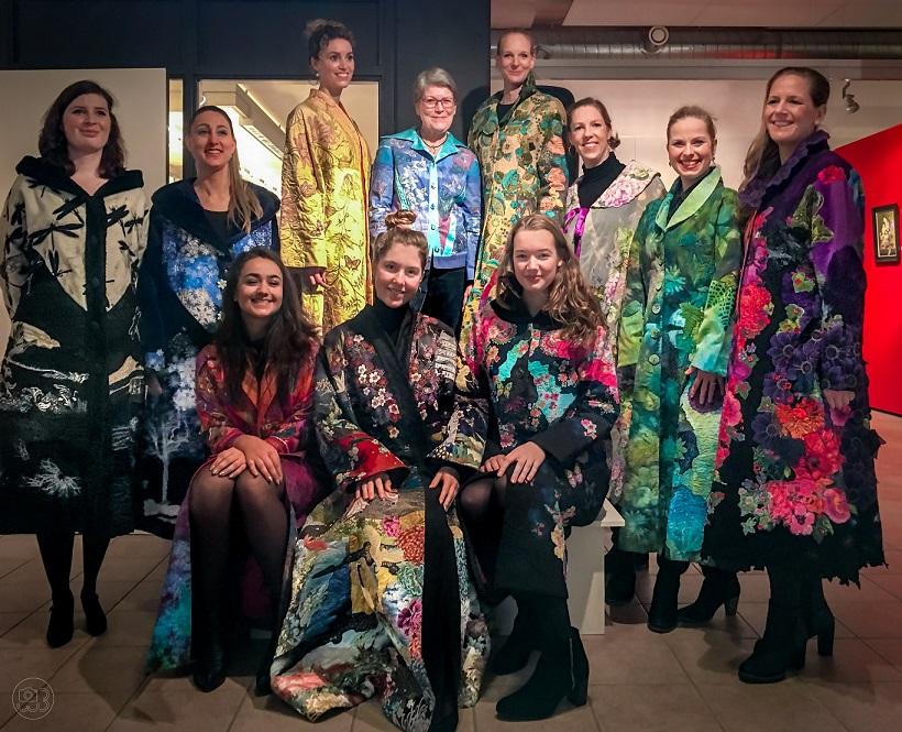 Marijke van Welzen te midden van de modellen die haar jassen showden tijdens de opening van de tentoonstelling. Fotograaf: Wicher Bos.