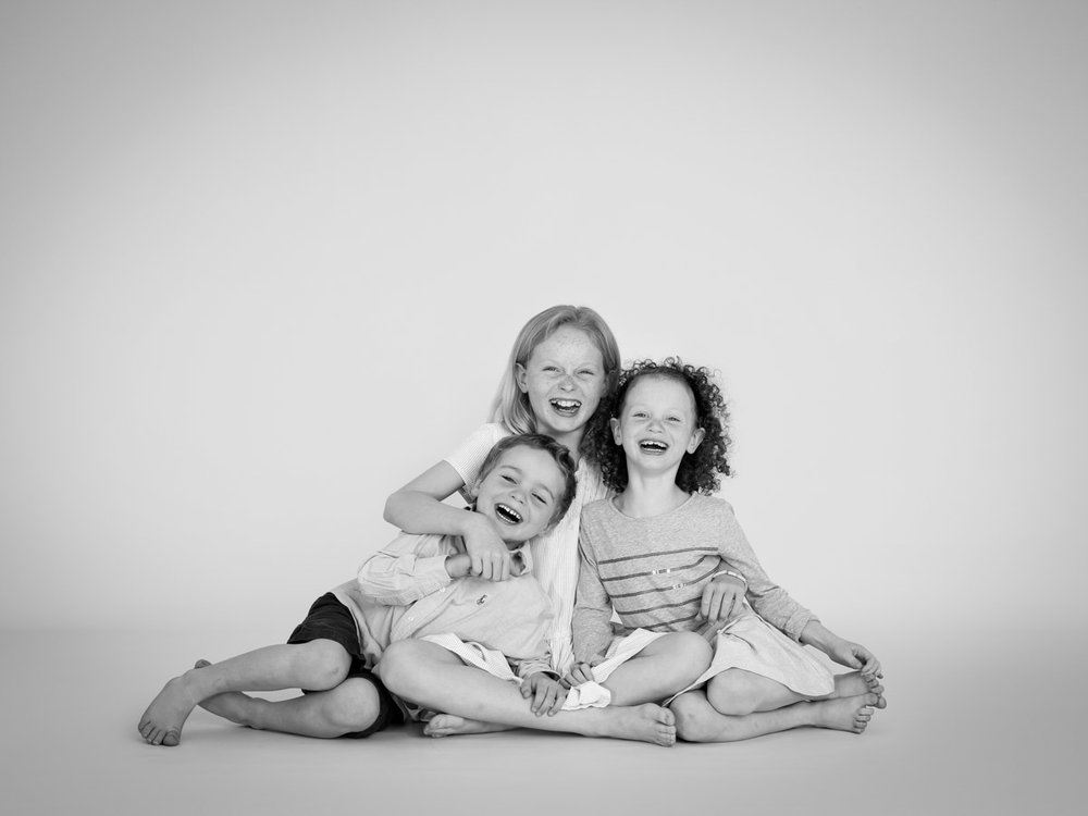 Three siblings laughing together