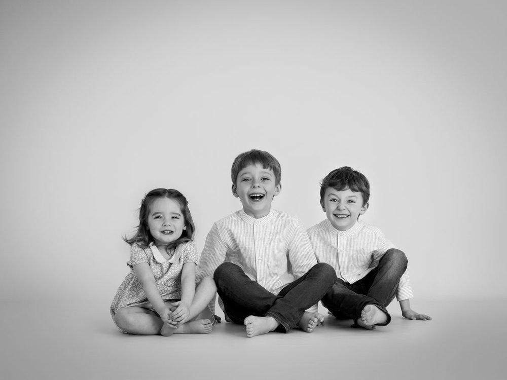 Copy of siblings sat on the floor laughing