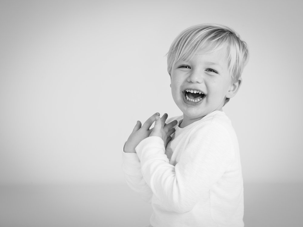Blonde boy laughing during his photo portrait