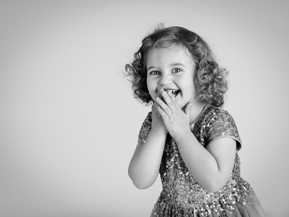 A young girl laughing at the photographer