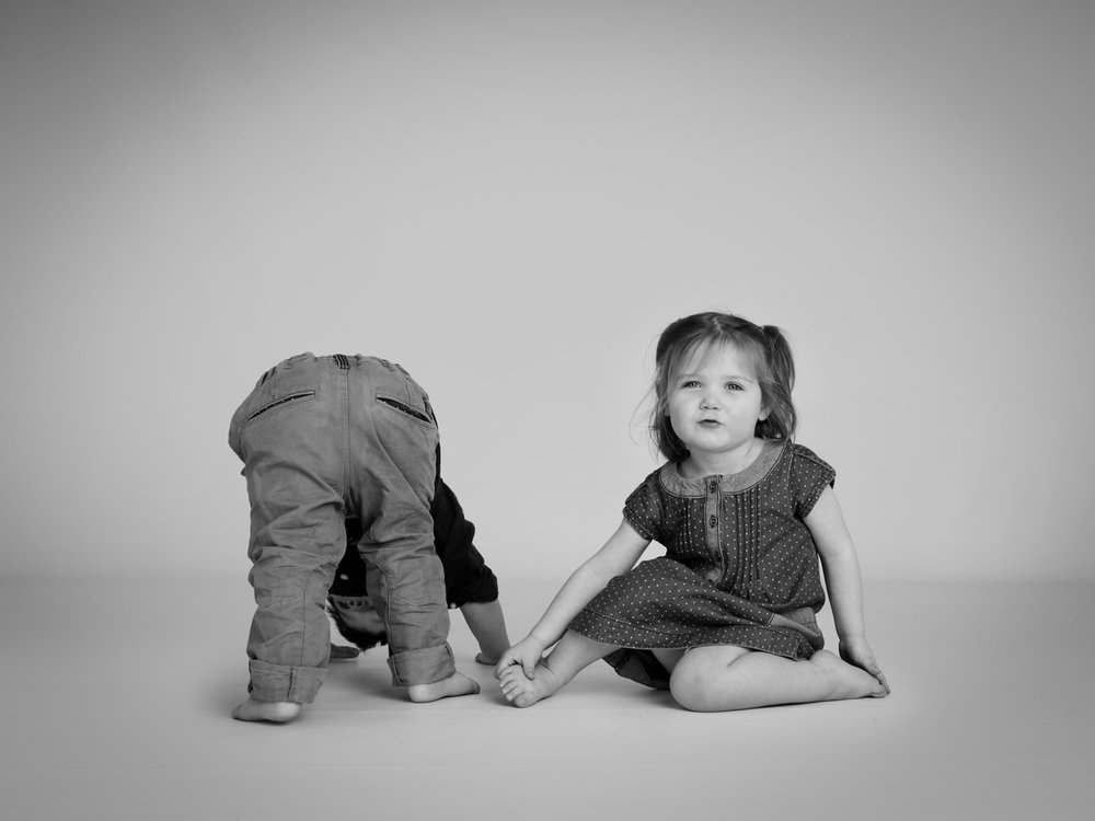 Two siblings playing during their photoshoot