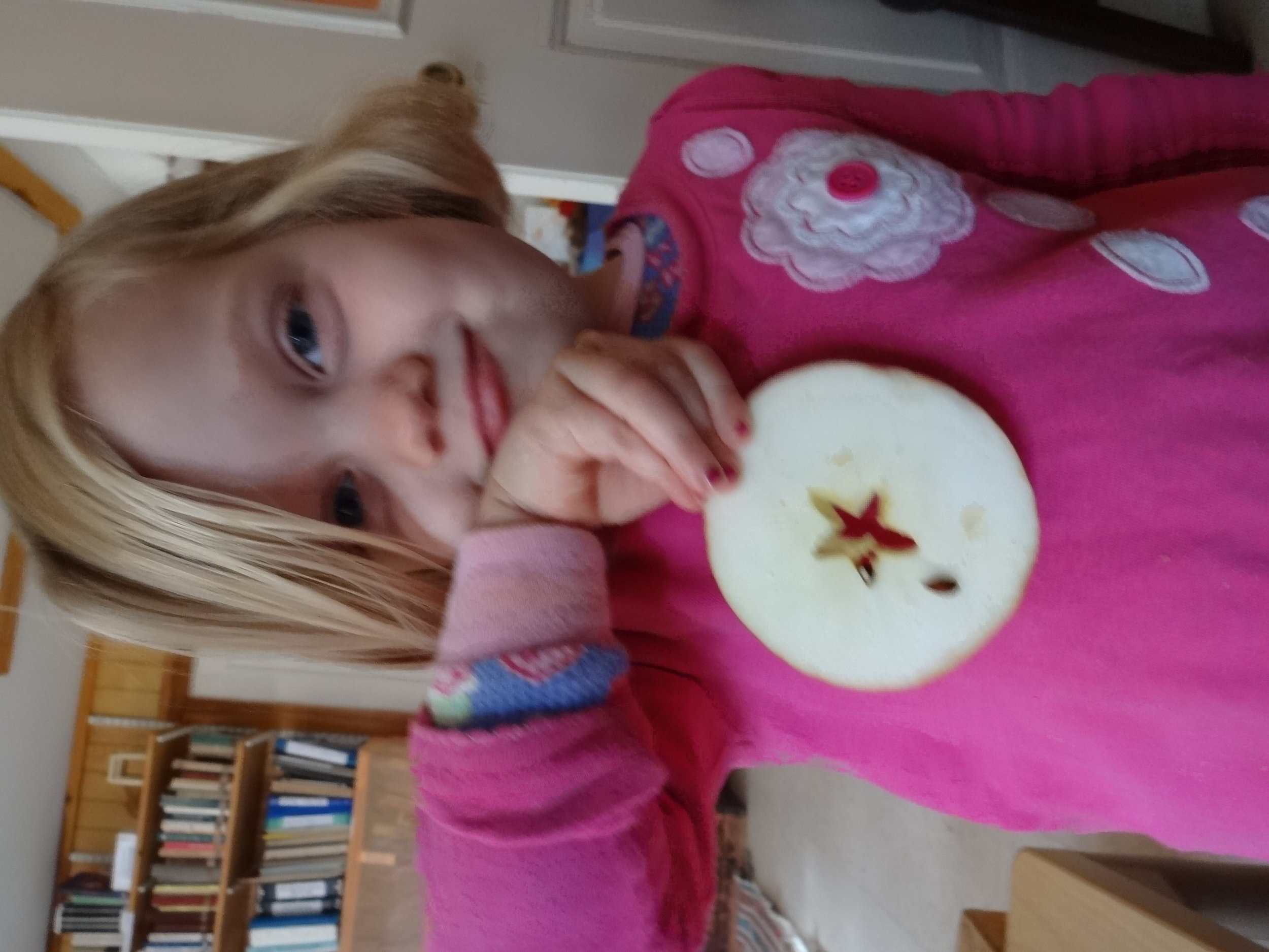 "Vera holding a ""star"" in the apple that was sliced into rings."