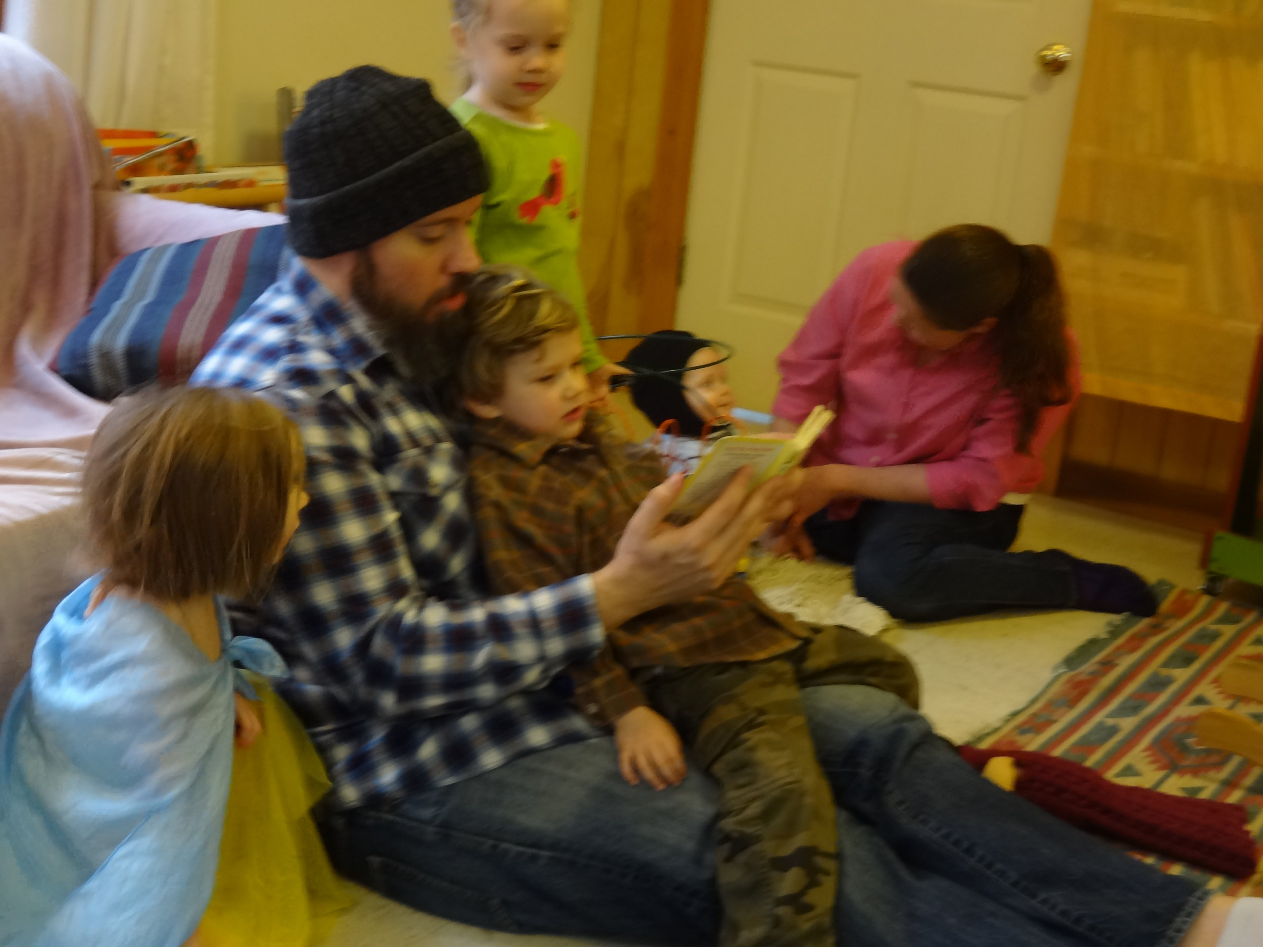 Brad is visiting with Cassian. Children enjoyed reading books with him.