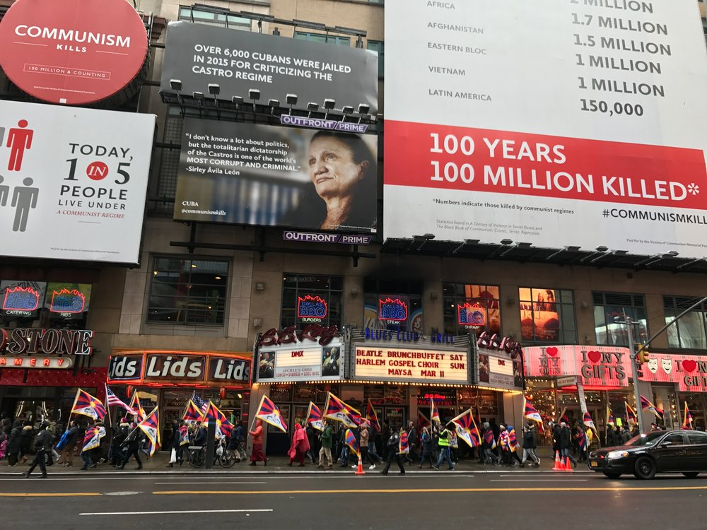 Tibetan activists march for freedom beneath VOC's billboards in Times Square.
