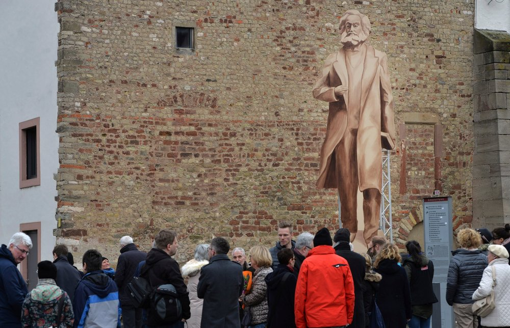 A conceptual representation of a statue of Karl Marx stands in the town square of Trier, Germany, the city where Marx was born in 1818. This wooden stand-in was erected to give residents an idea of how a bronze statue — a gift from the Chinese Communist Party — would look. Credit:  Harald Tittel/Picture-Alliance , via the  New York Times