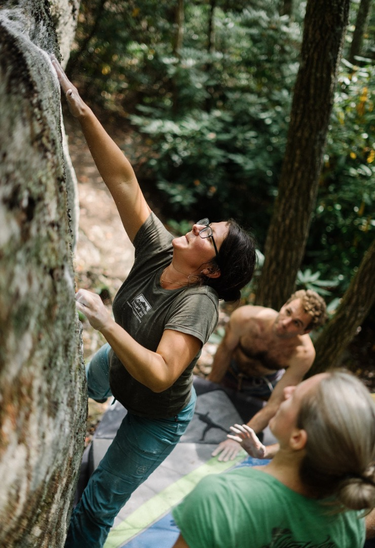 Access Fund conservation team member Andrea Hassler climbing during the Hound Ears Triple Crown event with Southeast Regional Director Zachary Lesch-Huie spotting. Photo courtesy of  On The Road and Off .