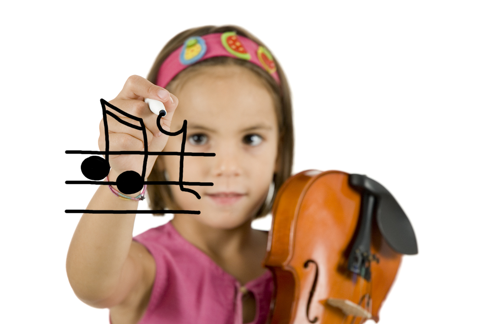 little girl writing with a pen and holding a violin isolated on white background.jpg