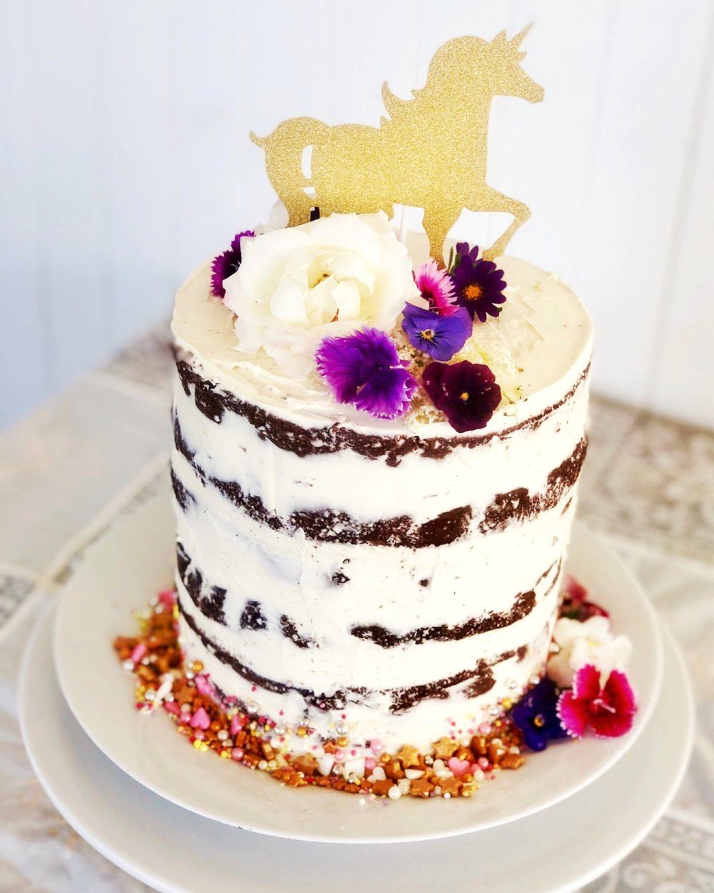 CELEBRATION CAKE$100 - Our chef can customise a beautiful semi-naked style celebration cake adorned with fresh flowers to provide a decadent finale to your child's party. Serves up to 30 people.
