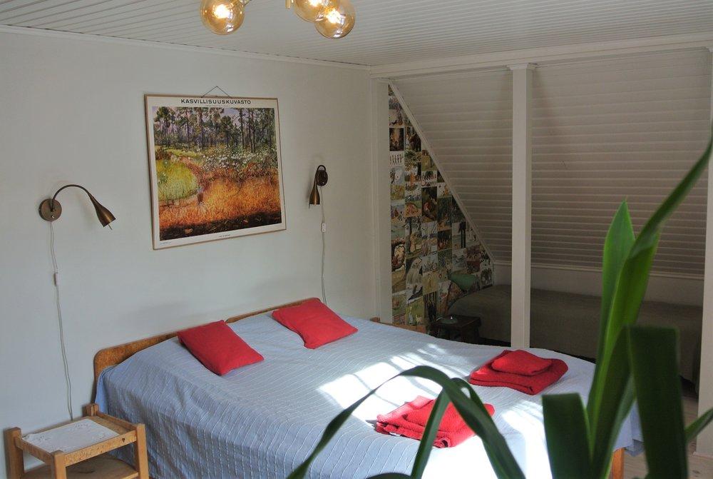 Punainen huone - Punaisessa huoneessa on tilaa kahdelle henkilölle kaksoissängyssä, ja lapsella lisäsängyssä. Punainen huone tykkää kotieläimistä!Punainen huone rakennettiin vuoden 1962 peruskorjauksen yhteydessä ja se toimi makuuhuoneena talon isäntäparille, kunnes he eivät enää jaksaneet nousta ylös rappuja. Vanhat punaiset tapetit ovat olleet huoneessa sitten peruskorjauksen ja antaneet nimen huoneelle. Huone peruskorjattiin 2018.
