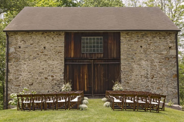 The barn on their property was a great backdrop for their wedding ceremony. Inside the barn were several vintage VW bugs and a VW bus! Photo by Captured by Missi.