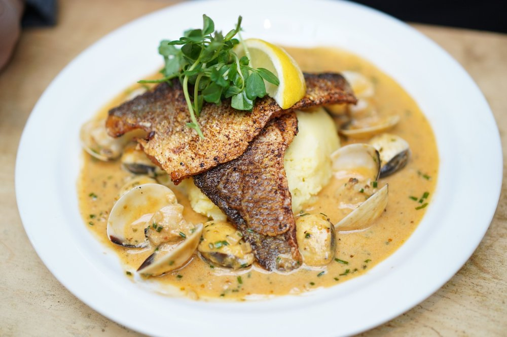 Pan fried seabass, feta mash, clam coconut herb sauce -