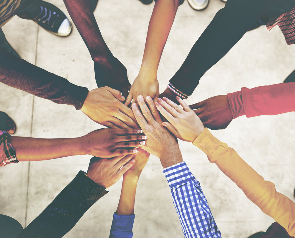 A circle of people of different ethnicities and genders joining hands in the center.