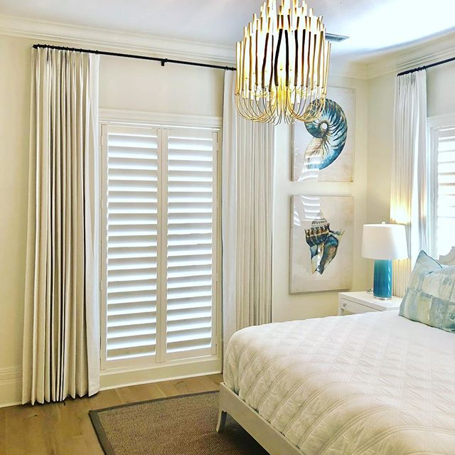 Layers of plantation shutters and tailored panels can warm up any decor.