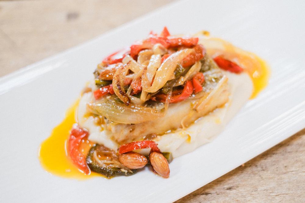 Bacalao encebollado sobre puré de batatas, almendras y pasas.