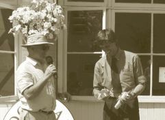 Peter Goodwin (with flowers growing out of his hat) gives Jim Colchester his pruning saw