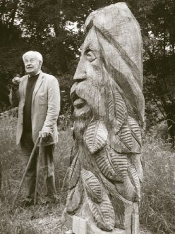"""John stands beside his sculpture """"The Spirit of the Woods"""". (Phil Hinton)"""