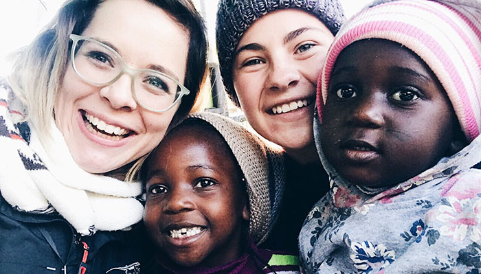 Two smiling American teens with smiling African childen Mission Travel .jpg