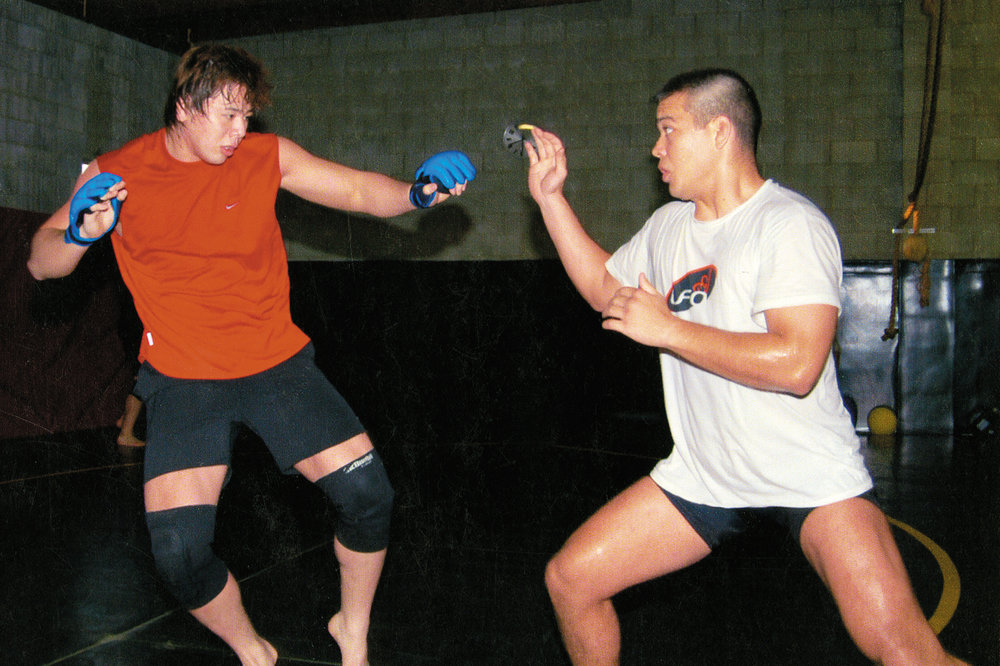 "Sparring with Lyoto Machida, currently active in UFC. ""This is a R.A.W. team training scene. I think it was probably before the Nortje fight [May 2, 2003]."" © 2014 SHINSUKE NAKAMURA / NEW JAPAN PRO WRESTLING / EAST PRESS."
