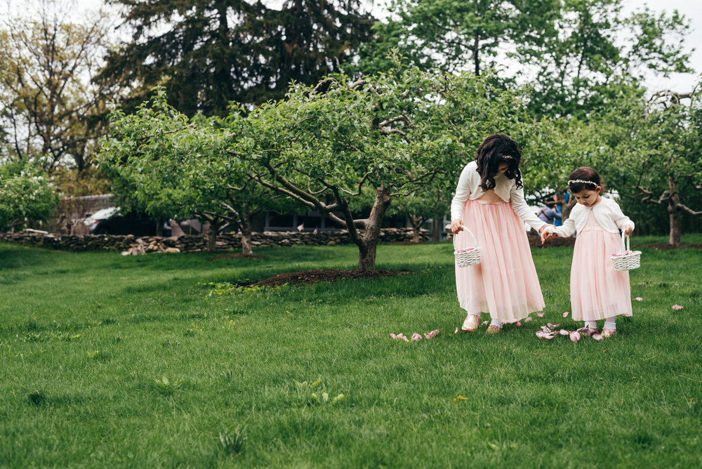 eddie's nieces were two of the flower girls for the wedding ceremony. But the older sister had to help theyounger sister to make sure the distribution of flower petals was just right as theyw alked down the grass to the aisle.