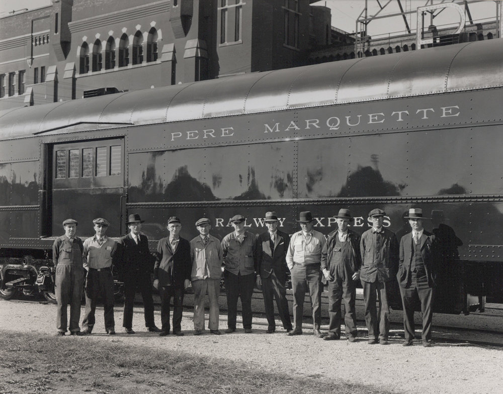 "This photo is believed to be taken right after an inspection of a rail car ordered by the Pere Marquette rail line.  The men pictured were likely foremen involved in its production.  The man on the right is believed to be a representative of the rail line.  He likely made a visit to the fourth floor of the 300 building, which was called the ""booze floor"" to sip whiskey before inspecting the car and taking delivery."