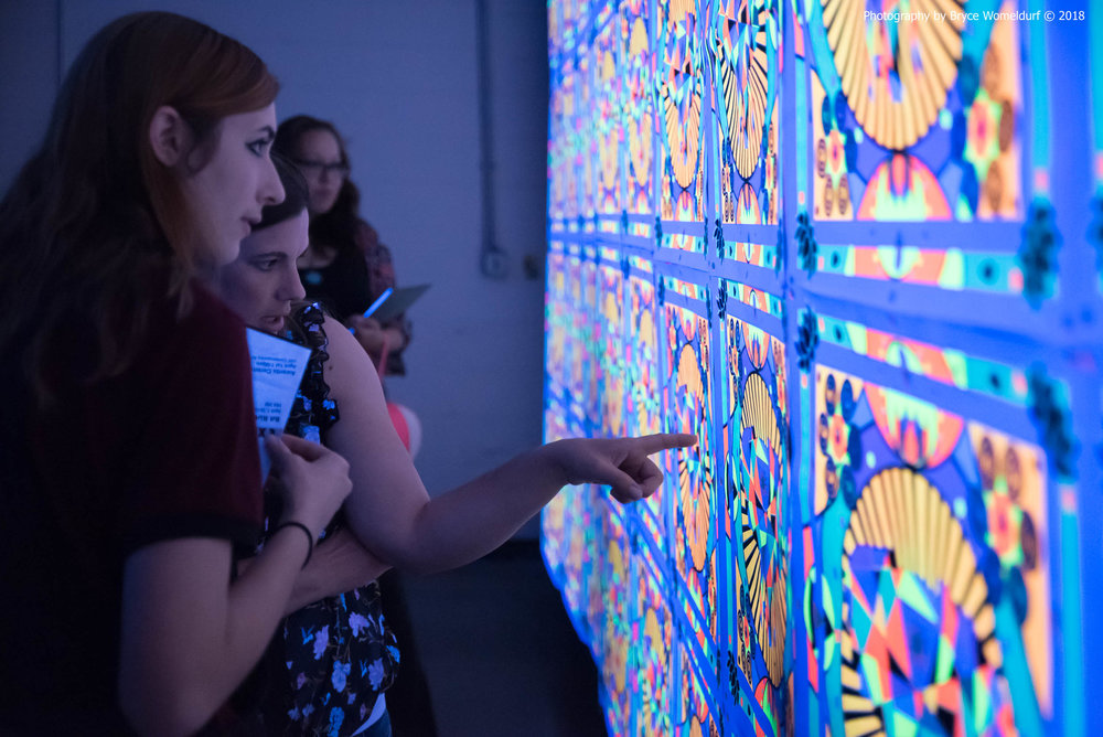 Attendees at USF's ArtHouse 2016 event check out the blacklight print area