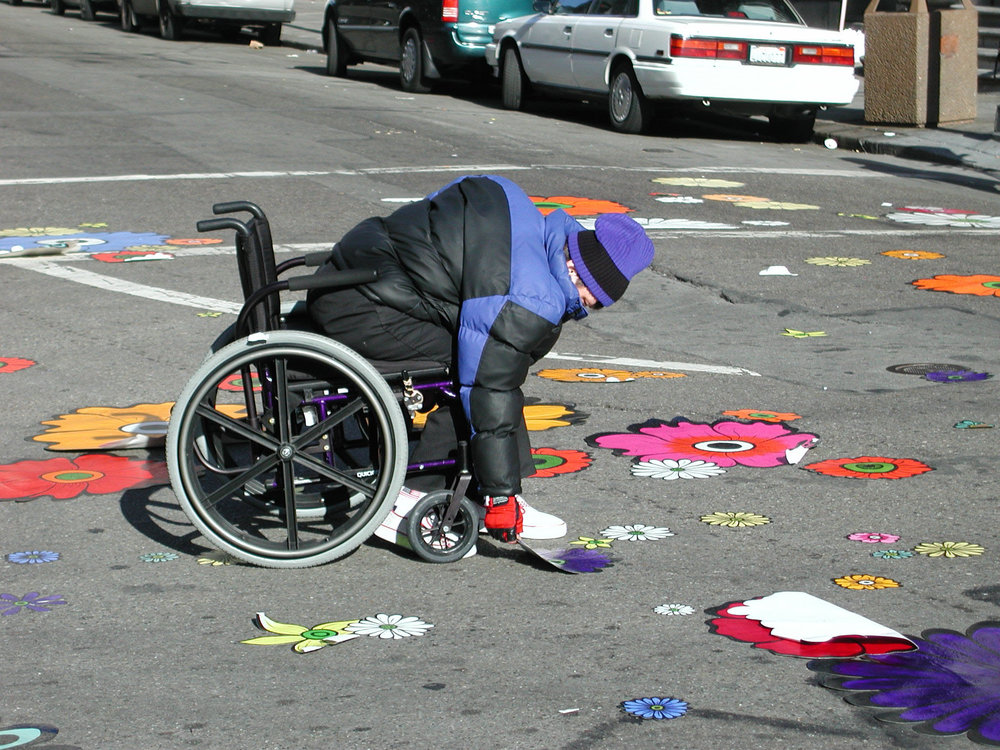 different man in wheelchair picking up flowers.jpg