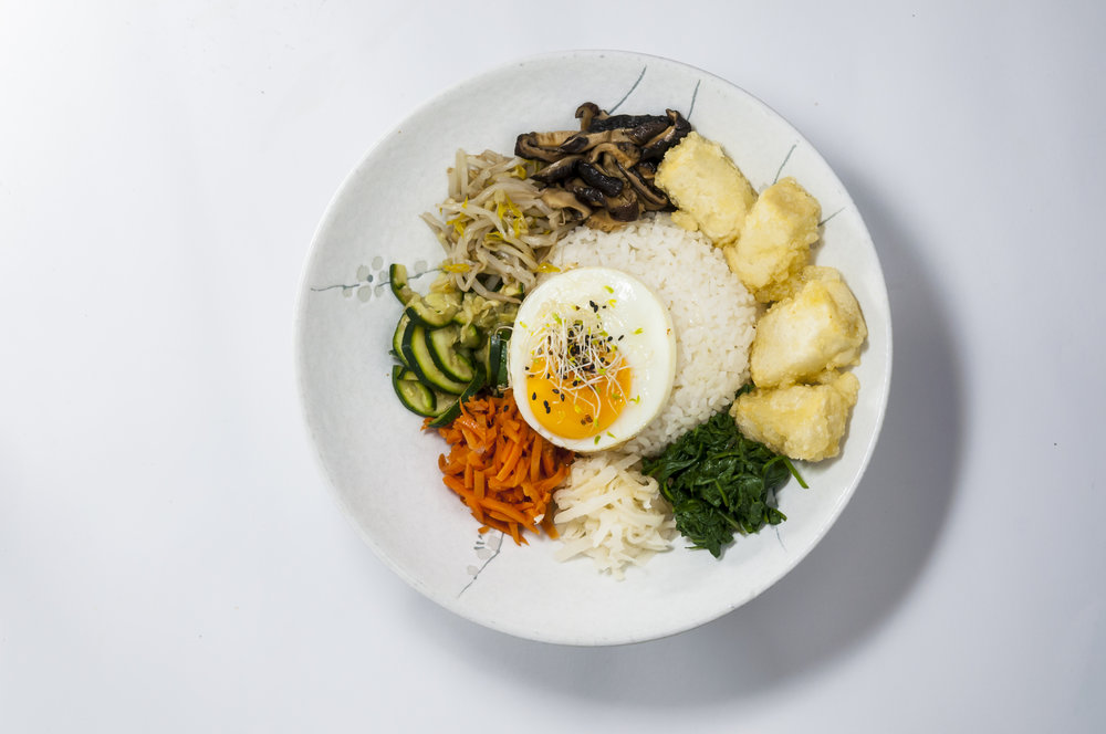 BIBIMBAB - A signature Korean dish. Bibimbap is served as a bowl of warmrice topped with sauteed and seasoned vegetables with chillipaste. For the best taste and aroma, we do recommend hot stoneBibimbap.