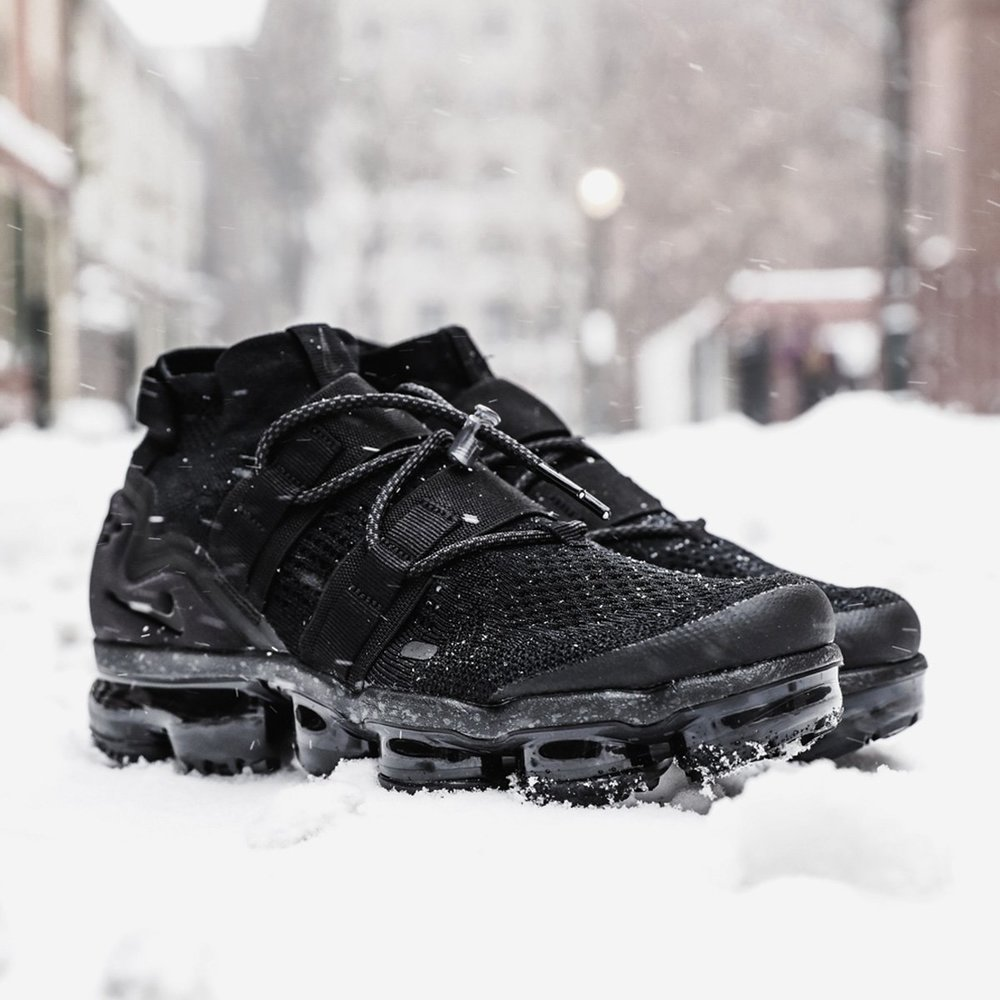 The cushy Air VaporMax Flyknit got a little bored of blacktop. Ravenous for more challenging terrain, the Utility stomped out from the woodland fog. The silhouette has grown to a three-quarter-high mid cut and has added a toggle lacing system and cushion foam midsole to jack up the support.