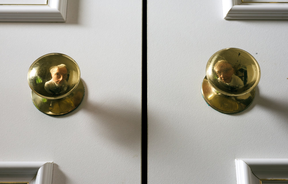 Selfie I - Face reflected by two wardrobe brass handles