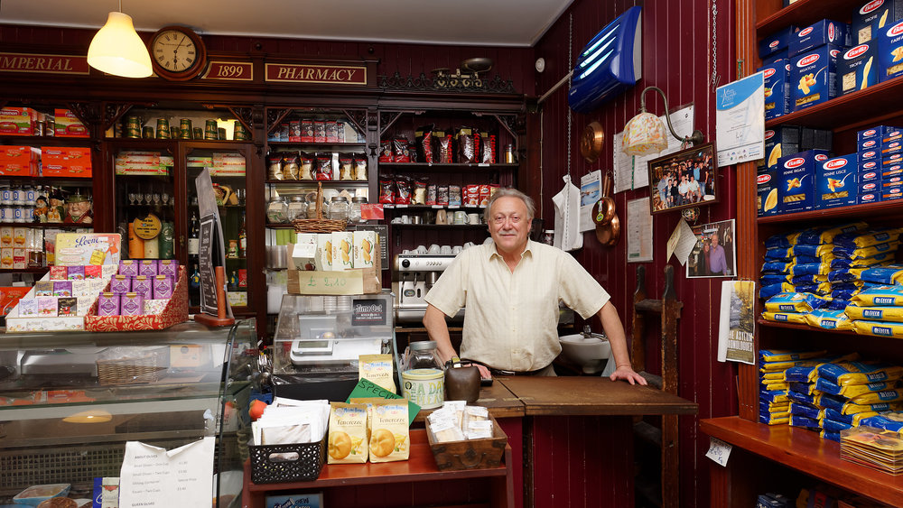 Giorgio Rafaelli behind the entrance to the serving area of his Italian delicatessen./cafe. Graham Land, 7th August, 2018