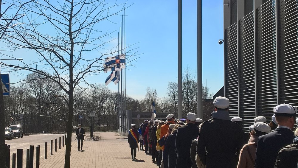 On Flora's Day 2017, the promovendi of the Faculty of Philosophy convened in Kumpula to elect the official wreath-weaver. President Mauno Koivisto had passed away the night before, and the day was overshadowed by flags at half-mast. The Student Union had awarded President Koivisto the badge of the Student Union's presiding officers in a broad purple ribbon in 1981.  Photo: Juha Hurme, 2017