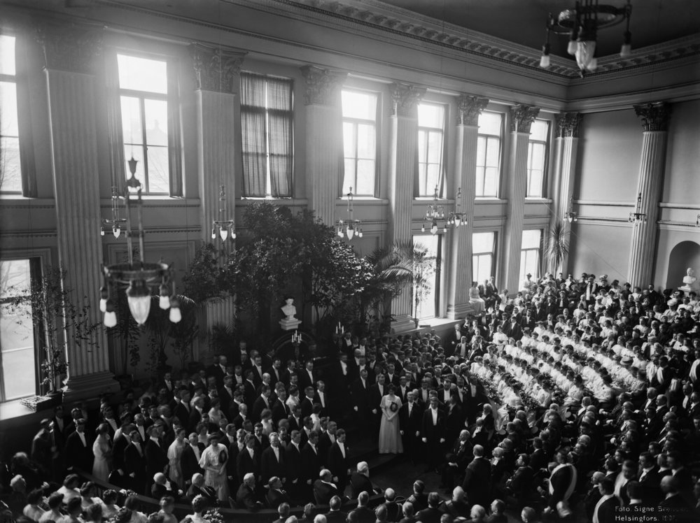 The conferment ceremony of the Faculty of Philosophy at the Imperial Alexander University in Finland filled the University's great hall in 1907. Professor Fridolf Gustafsson acted as the conferrer. The graduates received their academic insignia, the master's ring and laurel wreath, in the ceremony. In the photo, the great hall is shown in its old form, which was destroyed in the bombings of Helsinki in 1944.  Photo: Signe Brander, Helsinki City Museum, 1907.