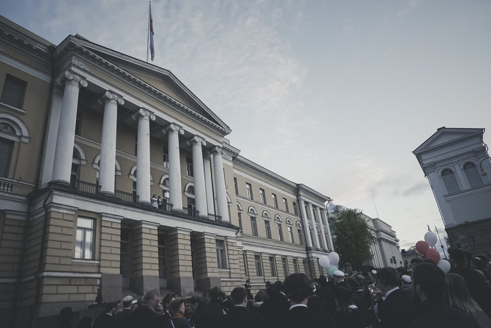 The conferment ceremony of the Faculty of Philosophy ends after a nocturnal procession in a speech made to the rising sun in front of the Main Building of the University of Helsinki. After the flag is raised, the participants also often sing Finlandia.  Photo: Juuso Koivisto, 2017.