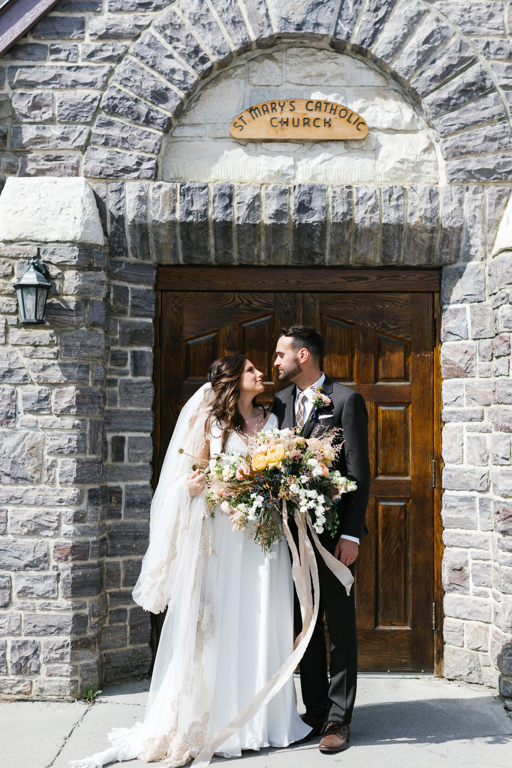 Photos by Shannon Yau  Our Calgary couple, Riley + Regan, traveled to the charming mountain church of St. Mary's in Banff and Cornerstone Theatre in Canmore for their magical mountain wedding where florals played a leading role.