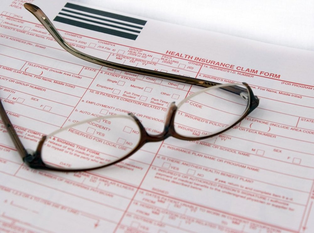 Glasses laying on top of a health insurance claim form