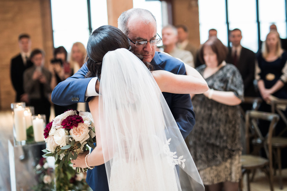 Dad hugging his daughter after they walked down the aisle together.