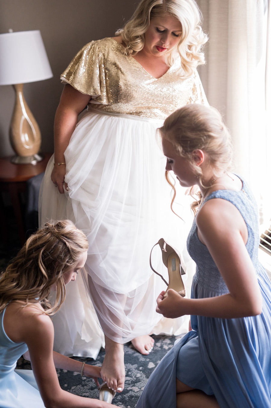 Bride putting her wedding shoes on.