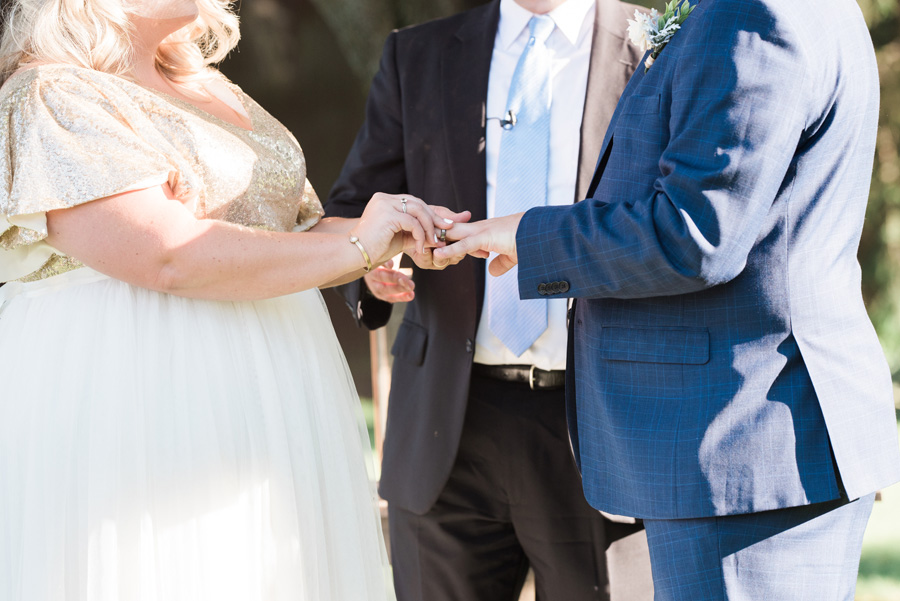 Bride and groom exchange rings during their outdoor wedding ceremony.