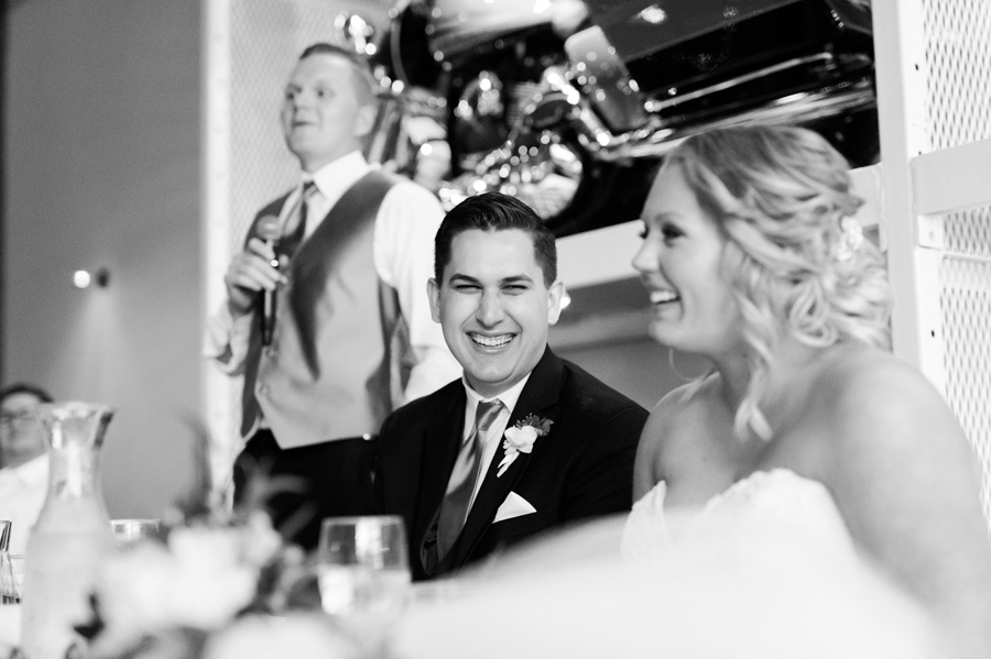 Bride and groom react to speech at reception.